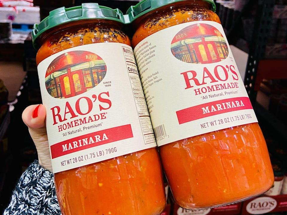 A hand holding a two-pack of Rao's marinara sauce from Costco