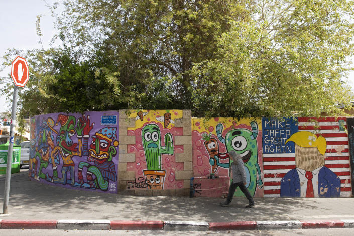 Graffiti adorns a wall in the Jaffa neighborhood of Tel Aviv, Israel, Wednesday, April 21, 2021. Historic Jaffa's rapid gentrification in recent years is coming at the expense of its mostly Arab lower class. With housing prices out of reach, discontent over the city's rapid transformation into a bastion for Israel's ultra-wealthy is reaching a boiling point. (AP Photo/Sebastian Scheiner)