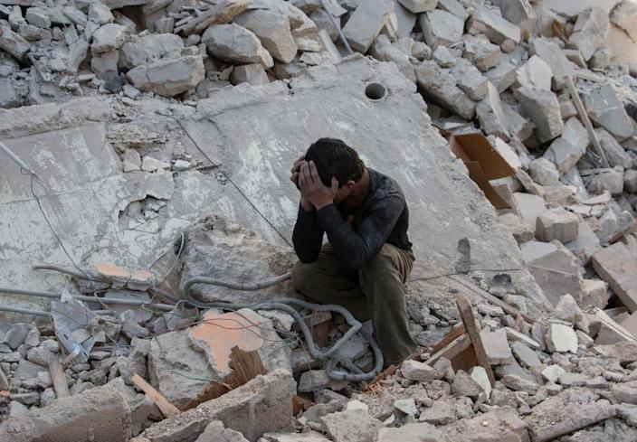 A Syrian boy mourns in the rubble of a building following a reported air strike by government forces on the rebel held area in the east of the northern Syrian city of Aleppo on April 13, 2015 (AFP Photo/Karam al-Masri)