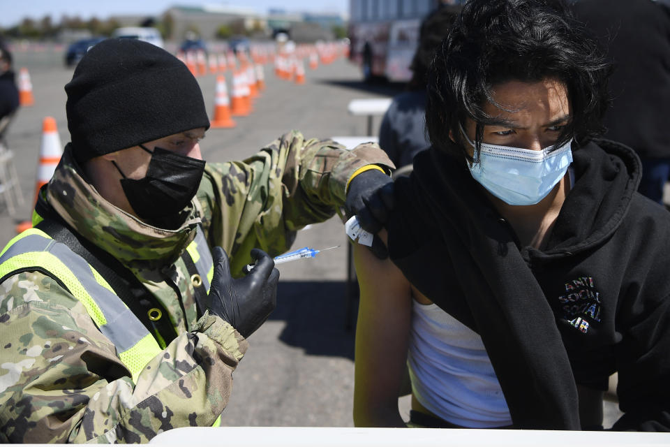 FILE - In this April 26, 2021, file photo Connecticut National Guard medic Todd Smith, left, administers a shot to East Hartford High School senior Alberto Salazar Rodriguez at a mass vaccination site at Pratt & Whitney Runway in East Hartford, Conn. Over the past year, National Guard members have been called in to battle the COVID-19 pandemic, natural disasters and race riots. (AP Photo/Jessica Hill, File)