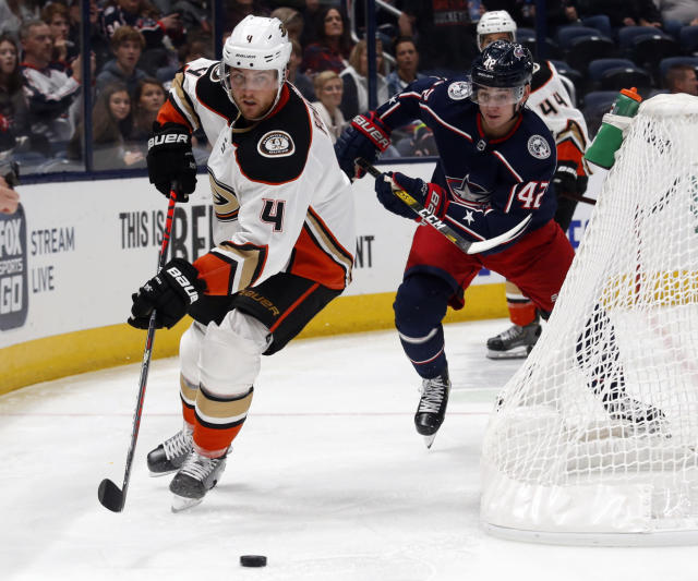 Anaheim Ducks defenseman Cam Fowler, left, controls the puck in front of Columbus Blue Jackets forward Alexandre Texier, of France, during the second period of an NHL hockey game in Columbus, Ohio, Friday, Oct. 11, 2019. (AP Photo/Paul Vernon)