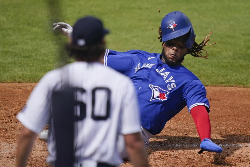 New York Yankees' Asher Wojciechowski (60) watches as Toronto Blue Jays' Vladimir Guerrero Jr. scores on Jonathan Davis single during the third inning of a spring baseball game Sunday, Feb. 28, 2021, in Tampa, Fla. (AP Photo/Frank Franklin II)