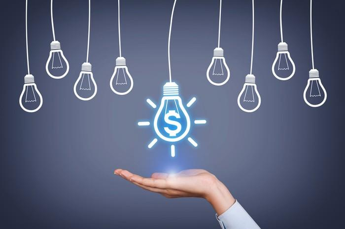 A hand being held out with a cartoon light bulb containing a dollar sign within it sitting on top.