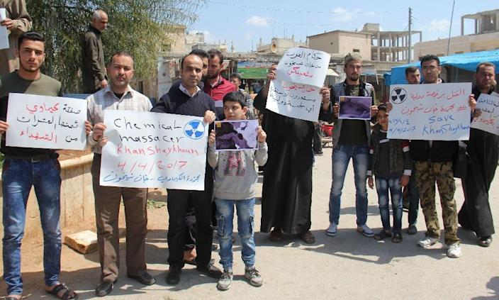 Syrian residents of Khan Sheikhun hold placards and pictures on April 7, 2017 during a protest condemning a suspected chemical weapons attack on their town (AFP Photo/Omar haj kadour)