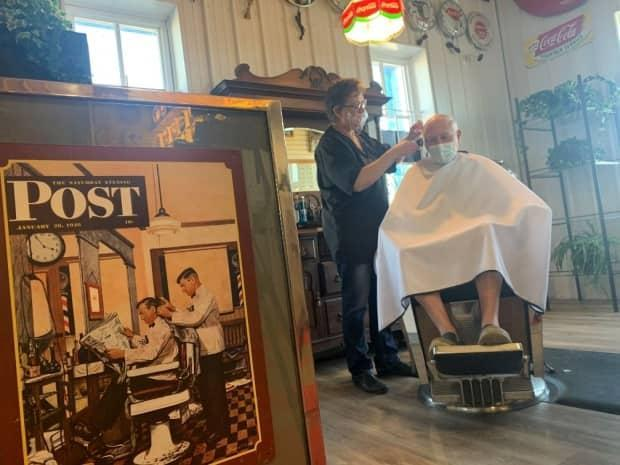 Dee Green, owner of Pioneer Barber Shoppe, cuts a client's hair at the store's new location in High River's Call of the West Museum.  (Terri Trembath/CBC - image credit)