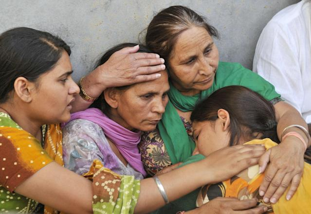 AMRITSAR, INDIA - MAY 2: Dalbir Kaur, sister of Sarabjit Singh an Indian prisoner in Pakistan who died in Pakistan hospital after being attacked by fellow inmates console his wife Sukhpreet Kaur, wife and daughters Swapandeep and Poonam at their native house on May 2, 2013 in Bikhiwind about 40 Kms from Amritsar, India. Sarabjit was arrested in 1990 after bombings in Lahore and Faisalabad that killed 14 people and was convicted of spying and carrying out the bomb blasts. His family maintained Singh was innocent and had entered Pakistan inadvertently from his hometown of Bhikiwind in northern Punjab state bordering Pakistan. (Photo by Munish Byala/Hindustan Times via Getty Images)