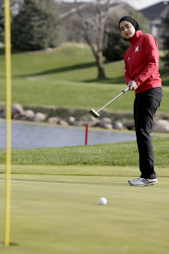 In this April 10, 2019 photo, Noor Ahmed, a member of the Nebraska NCAA college golf team, putts during a practice session in Lincoln, Neb. Ahmed is the only golfer at the college level or higher known to wear a hijab while competing. She hopes Muslim girls are watching her and encouraged to chase their dreams in environments where they might encounter fear, uncertainty and hostility. (AP Photo/Nati Harnik)