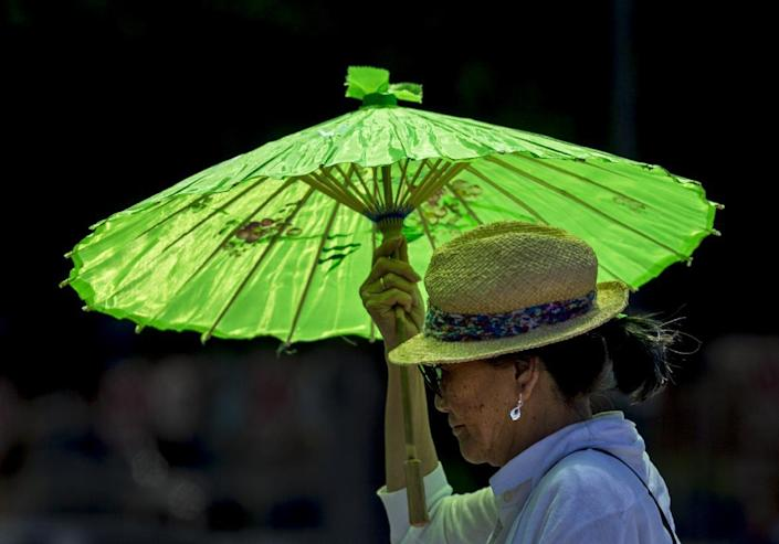 A pedestrian shields under a parasol from the hot sun in the Echo Park district in Los Angeles Wednesday, May, 14, 2014. A heat wave gripped California compounding the critical drought conditions across the state. (AP Photo)