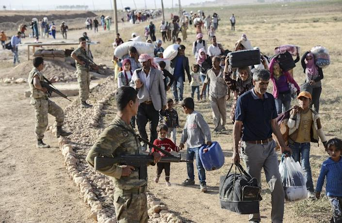 Syrian Kurds walk by Turkish soliders after crossing into Turkey near the southeastern town of Suruc in Sanliurfa province, on September 19, 2014 (AFP Photo/Ilyas Akengin)