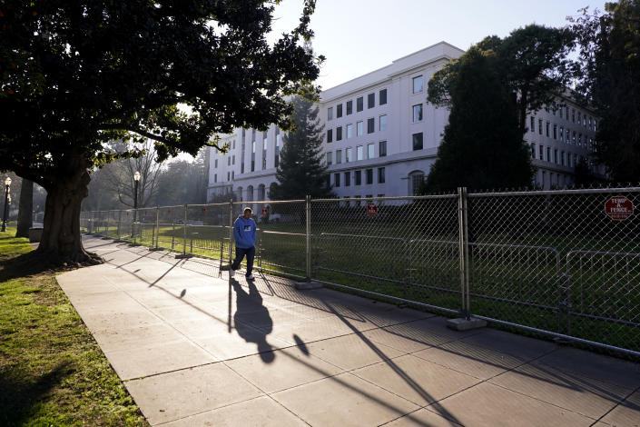 A temporary six-foot high chain link fence surrounds the state Capitol because of concerns over the potential for civil unrest, in Sacramento, Calif., Thursday, Jan. 14, 2021. With the FBI warning of potential violence at all state capitols Sunday, Jan. 17, the ornate halls of government and symbols of democracy looked more like heavily guarded U.S. embassies in war-torn countries. (AP Photo/Rich Pedroncelli)