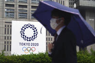 A man wearing a protective mask to help curb the spread of the coronavirus walks in the rain past a banner of Tokyo 2020 Olympic Games Thursday, May 13, 2021, in Tokyo. The Japanese capital confirmed more than 1,000 new coronavirus cases on Thursday. (AP Photo/Eugene Hoshiko)