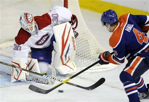 Edmonton Oilers' Taylor Hall, right, shoots on Montreal Canadiens goalie Peter Budaj during the second period of an NHL hockey game, Thursday, March 8, 2012, in Edmonton, Alberta. (AP Photo/The Canadian Press, John Ulan)