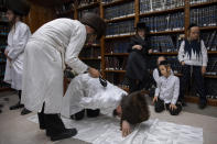 An ultra-Orthodox Jewish man whips a member of his Hasidic dynasty with a leather strap as a symbolic punishment for his sins last year, during the traditional Malkot (whipping in Hebrew) ceremony, ahead of Yom Kippur that begins at sunset, in the city of Beit Shemesh, near Jerusalem, Wednesday, Sept. 15, 2021. Yom Kippur is Judaism's day of atonement, when devout Jews ask God to forgive them for their transgressions and refrain from eating and drinking, attending intense prayer services in synagogues. (AP Photo/Oded Balilty)