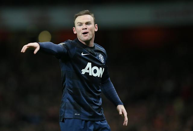 Manchester United's Wayne Rooney gestures to his teammates during their English Premier League soccer match between Arsenal and Manchester United at the Emirates stadium in London, Wednesday, Feb. 12, 2014. (AP Photo/Alastair Grant)