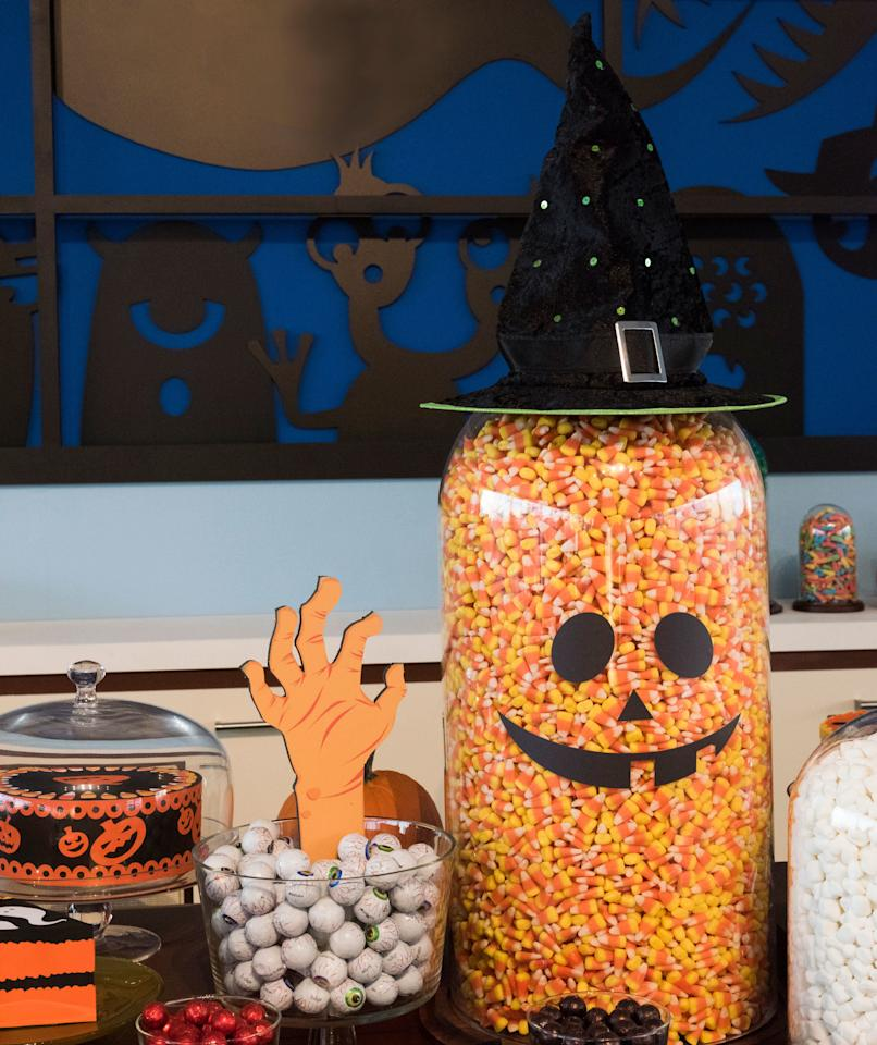 """<p>When the kids are over for the Halloween party, you might not want to get too macabre (or risk scaring the little ones). Throw a silly, colorful, and whimsical party instead. """"Use iconic Halloween candy as décor!"""" Stark says. """"You can fill bowls with eyeball candy and add monster' hands reaching out. One of our favorite tricks is to turn classic bell jars into pumpkins' and ghosts.'"""" Display all the candy out on a buffet and encourage guests to help themselves by providing take home treat bags. Party trick: It may look like he used a lot of candy corn to fill the large cloche, but he actually added bubble wrap to the center of the container to make it look fuller.</p>"""