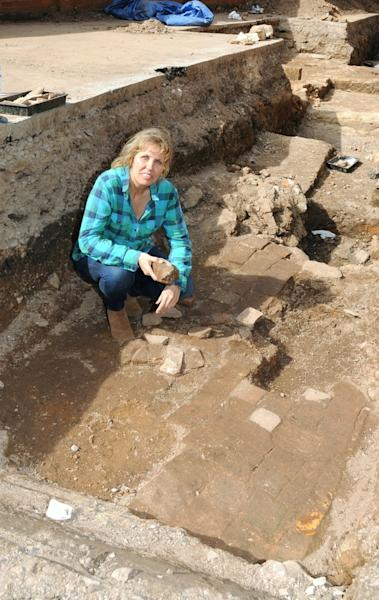 Richard III society member Philippa Langley crouches amid paving stones which may belong to a 17th-century garden containing a memorial to the lost king.