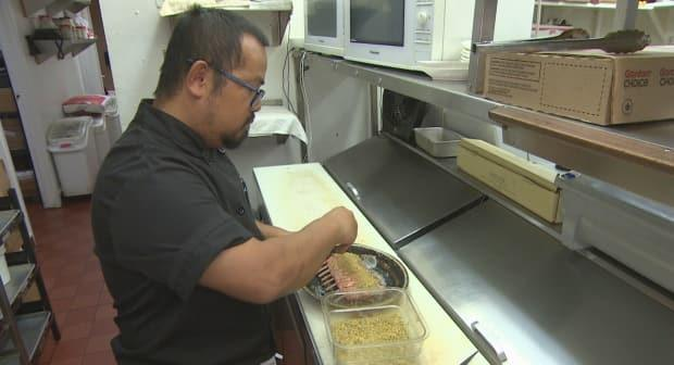A cook works in the kitchen at Memories Dining and Bar in Regina. The restaurant's owner says this summer's drought in the Prairies has driven up food costs. (Richard Agecoutay/CBC - image credit)