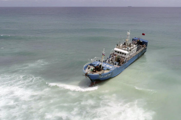 A view of the FV Lu Rong Yuan Yu, a Chinese-flagged fishing vessel that ran aground at Pointe-aux Sables, Port-Louis, Mauritius, Monday, March 8, 2021. Workers in Mauritius have begun pumping 130 tons of fuel from a Chinese fishing vessel that ran aground on a coral reef on the Indian Ocean island's west coast on Sunday. Local newspaper L'Express reported that the grounded ship has spilled a small amount of fuel into the ocean, but its hull remains intact. (L'express Maurice via AP)