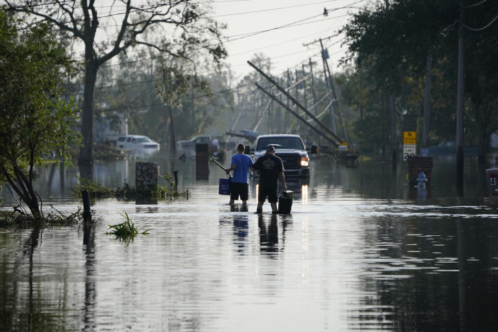 People walk up a street flooded in the aftermath of Hurricane Ida, Wednesday, Sept. 1, 2021, in Jean Lafitte, La. Louisiana residents still reeling from flooding and damage caused by Hurricane Ida are scrambling for food, gas, water and relief from the oppressive heat. (AP Photo/John Locher)