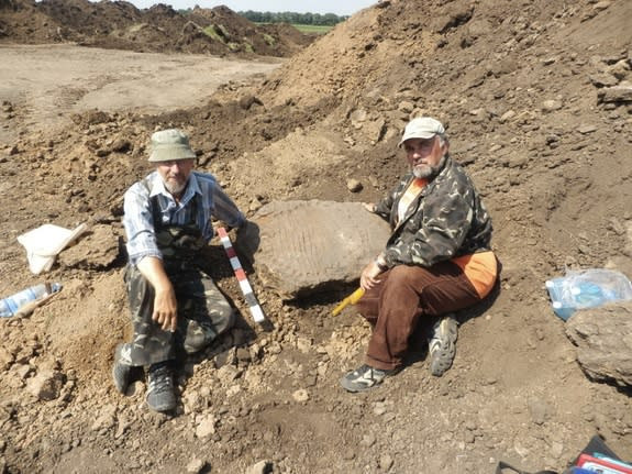 Archaeologists pose with a Bronze Age sundial dating back more than 3,000 years.