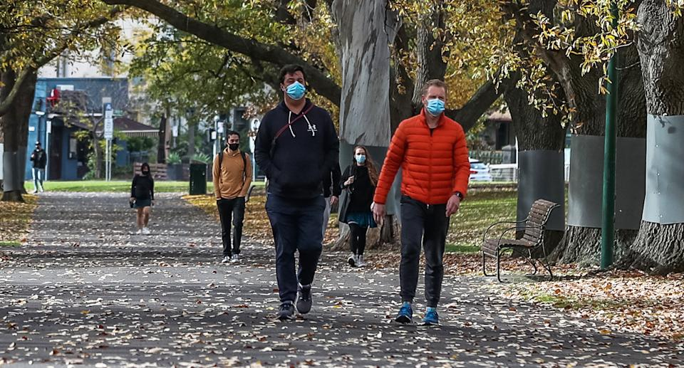 People with face masks walk through a park in Melbourne during Covid lockdown.