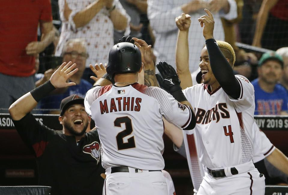 Arizona Diamondbacks' Jeff Mathis (2) celebrates his two-run home run against the Chicago Cubs with Ketel Marte (4) and David Peralta, left, during the eighth inning of a baseball game Wednesday, Sept. 19, 2018, in Phoenix. The Diamondbacks defeated the Cubs 9-0. (AP Photo/Ross D. Franklin)