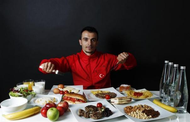 Turkish weightlifter and Olympic hopeful Mete Binay, 27, poses in front of his daily meal intake in Ankara May 29, 2012.
