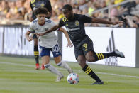 Columbus Crew's Kevin Molino, right, dribbles the ball next to D.C. United's Kevin Paredes during the first half of an MLS soccer match Wednesday, Aug. 4, 2021, in Columbus, Ohio. (AP Photo/Jay LaPrete)