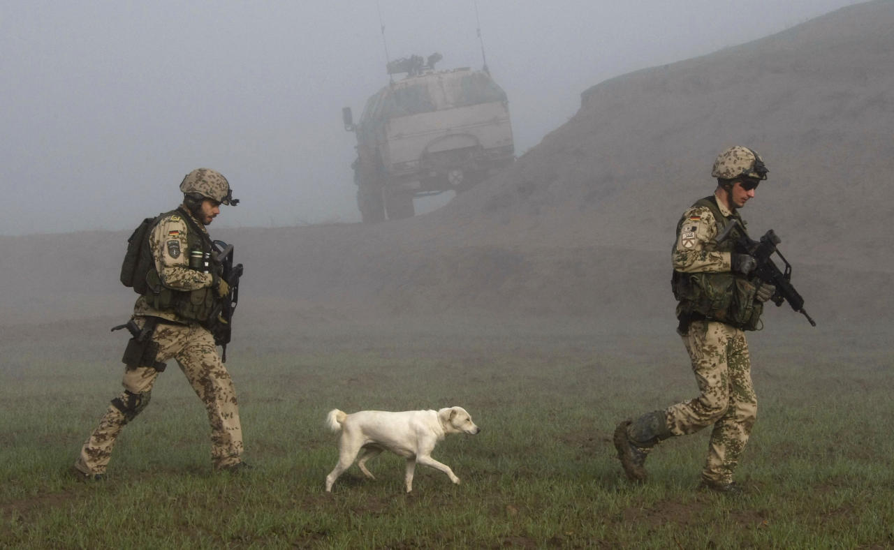 A dog follows German Bundeswehr army soldiers of the International Security Assistance Force (ISAF) during a mission in Chahar Dara in the outskirts of Kunduz, December 17, 2009. German Bundeswehr army soldiers and Afghan National Army (ANA) units started a operation against insurgents in the area on Wednesday. REUTERS/Fabrizio Bensch (AFGHANISTAN - Tags: MILITARY CONFLICT)