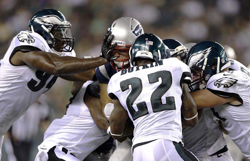 New England Patriots quarterback Tim Tebow, center, is tackled by Philadelphia Eagles, from left, defensive end Chris McCoy, cornerback Eddie Whitley, cornerback Brandon Boykin and linebacker Jake Knott during the second half of a preseason NFL football game on Friday, Aug. 9, 2013, in Philadelphia. (AP Photo/Matt Rourke)