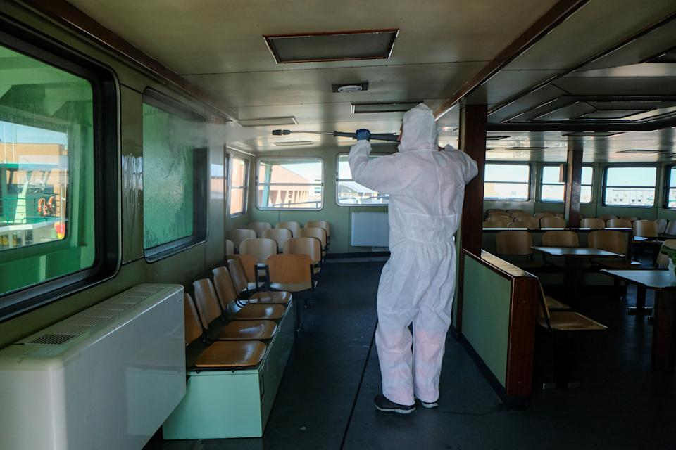 A man in a protective suit sanitises a water taxi as part of measures to try and contain a coronavirus outbreak, in Venice, Italy, February 28, 2020. REUTERS/Manuel Silvestri