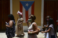 A group of activists march demanding statues and street names commemorating symbols of colonial oppression be removed, in San Juan, Puerto Rico, Saturday, July 11, 2020. Dozens of activists marched through the historic part of Puerto Rico's capital on Saturday to demand that the U.S. territory's government start by removing statues, including those of explorer Christopher Columbus. (AP Photo/Carlos Giusti)