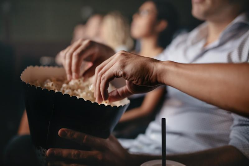 people eating popcorn in movie theater, focus on hands