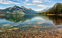 """<p>As the largest lake in Montana's photogenic Glacier National Park, <a href=""""http://www.visitmt.com/listings/general/lake/lake-mcdonald.html"""" rel=""""nofollow noopener"""" target=""""_blank"""" data-ylk=""""slk:Lake McDonald"""" class=""""link rapid-noclick-resp"""">Lake McDonald</a> spans 10 miles and sinks 472 feet deep. Formed by Ice Age-era glaciers, the lake has a still, reflective surface that provides the perfect mirror for the surrounding mountains. Visitors might even spot a bighorn sheep, elk, or black bear, as they are known to tour the area.</p>"""