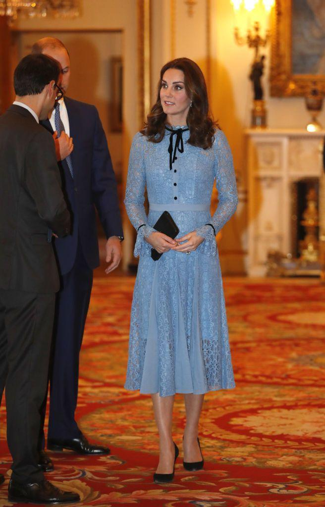 """<p>The Duchess made her first public appearance at a Buckingham Palace reception since announcing <a href=""""https://www.townandcountrymag.com/society/tradition/a12167619/kate-middleton-due-date-2018/"""" rel=""""nofollow noopener"""" target=""""_blank"""" data-ylk=""""slk:her third pregnancy"""" class=""""link rapid-noclick-resp"""">her third pregnancy</a>. Though Duchess Kate is still <a href=""""https://www.townandcountrymag.com/society/tradition/a12185279/kate-middleton-hyperemesis-gravidarum-morning-sickness-meaning/"""" rel=""""nofollow noopener"""" target=""""_blank"""" data-ylk=""""slk:suffering from Hyperemesis Gravidarum"""" class=""""link rapid-noclick-resp"""">suffering from Hyperemesis Gravidarum</a>, her light blue, Temperley dress set a cheery tone over her new <a href=""""https://www.townandcountrymag.com/society/tradition/a12810469/kate-middleton-baby-bump-photos/"""" rel=""""nofollow noopener"""" target=""""_blank"""" data-ylk=""""slk:baby bump"""" class=""""link rapid-noclick-resp"""">baby bump</a>. The knee-length, lace ensemble had black detailing in its front buttons and bowtie neckline, to which Kate matched a black clutch, black pumps, and a pair of blue topaz and diamond earrings by Kiki McDonough.</p>"""
