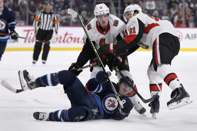 Winnipeg Jets' Mark Scheifele (55) is dropped to the ice by Ottawa Senators' Drake Batherson (19) and Ron Hainsey (81) during second period NHL action in Winnipeg on Saturday, Feb. 8, 2020. (Fred Greenslade/The Canadian Press via AP)
