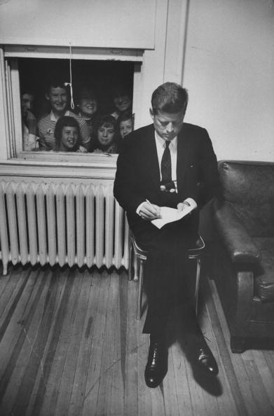 <p>Senator John F. Kennedy works, while an excited group of onlookers watches from the window.</p>