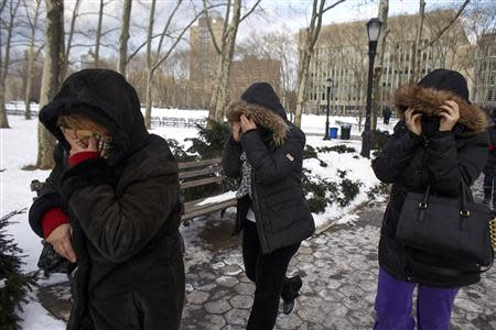 Family members of Vincent Asaro, an alleged leader of the Bonanno organized crime family, cover their faces as they leave the Federal courthouse in the Brooklyn borough of New York January 23, 2014. REUTERS/John Taggart