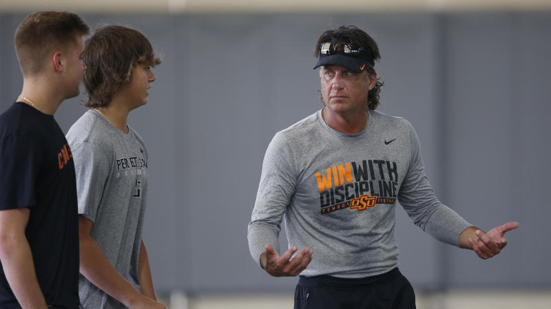 Oklahoma State head coach Mike Gundy, right, talks with his sons, Gunnar Gundy, left, and Gage Gundy, center, during an NCAA college football practice in Stillwater Okla., Tuesday, Aug. 6, 2019. (AP Photo/Sue Ogrocki)