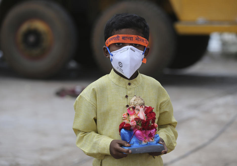 An Indian child wearing a mask as a precaution against the coronavirus carries an idol of elephant-headed Hindu god Ganesha to immerse in Saroornagar Lake on the final day of Ganesh Chaturthi festival in Hyderabad, India, Tuesday, Sept. 1, 2020. The festival is a celebration of the birth of Ganesha, the Hindu god of wisdom, prosperity and good fortune. (AP Photo/Mahesh Kumar A.)