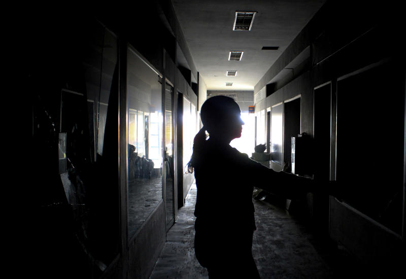 A mall employe inspects stores one day after the mall was looted, in Maracaibo, Venezuela, Wednesday, March 13, 2019. Venezuela's largest private food supplier says massive looting and vandalism occurred at four facilities in the city of Maracaibo during nationwide power outages, complicating efforts to distribute food and drinks to people in the area. (AP Photo/Henry Chirinos)