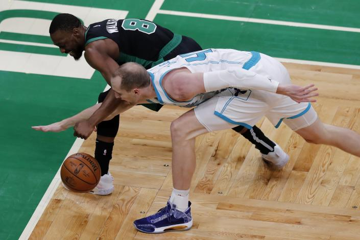 Boston Celtics' Kemba Walker (8) and Charlotte Hornets' Cody Zeller (40) battle for the ball during the first half of an NBA basketball game, Sunday, April 4, 2021, in Boston. (AP Photo/Michael Dwyer)
