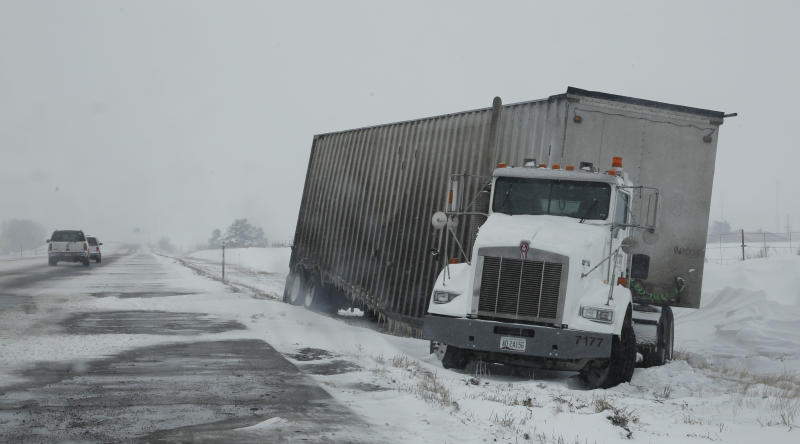 A tractor-trailer sits on the shoulder of Interstate 70 westbound after sliding off the icy highway near Watkins, Colo., as a spring storm packing high winds and heavy snow sweeps over Colorado's Front Range and on to the eastern plains on Saturday, March 23, 2013. Forecasters predict up to a foot of snow will fall in some locations in Colorado before the storm heads toward the nation's midsection. (AP Photo/David Zalubowski)