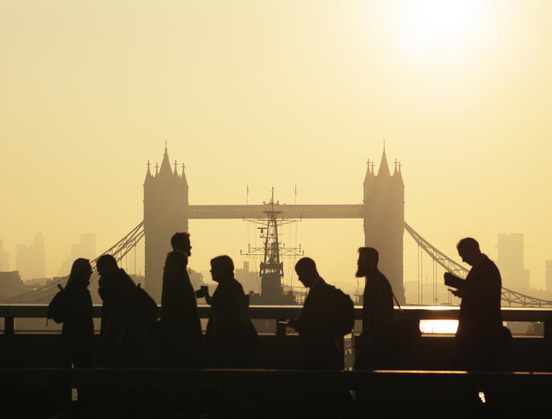 UK, London, silhouette of unrecognisable business people walking to work via London Bridge with view of Tower Bridge behind