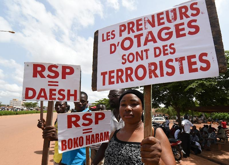 """A protester holds a sign reading """"Hostage takers are terrorists"""" and """"Regiment of Presidential Security (RSP) = Daesh and Boko Haram"""" during a protest in Ouagadougou on September 23, 2015 (AFP Photo/Sia Kambou)"""