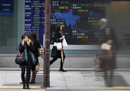 Pedestrians stand in front of a stock quotation board displaying stock prices outside a brokerage in Tokyo January 15, 2014. REUTERS/Yuya Shino