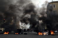 Protesters burn tires to block a road, during a protest in Beirut, Lebanon, Thursday, March 4, 2021. Lebanon has been hit by one crisis after another, with widespread protests against the country's corrupt political class breaking out in October 2019. (AP Photo/Bilal Hussein)