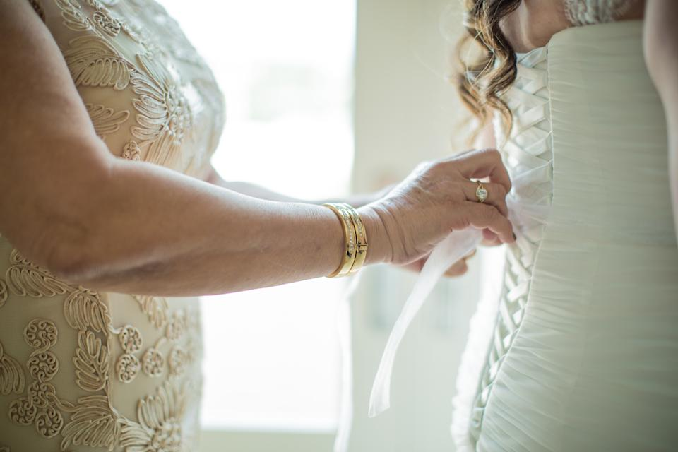 mother of the bride tying the back of a bride's white wedding dress