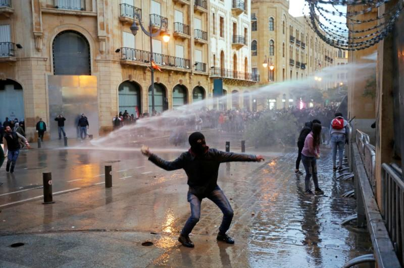 A demonstrator throws a stone as police use water cannon during a protest in Beirut