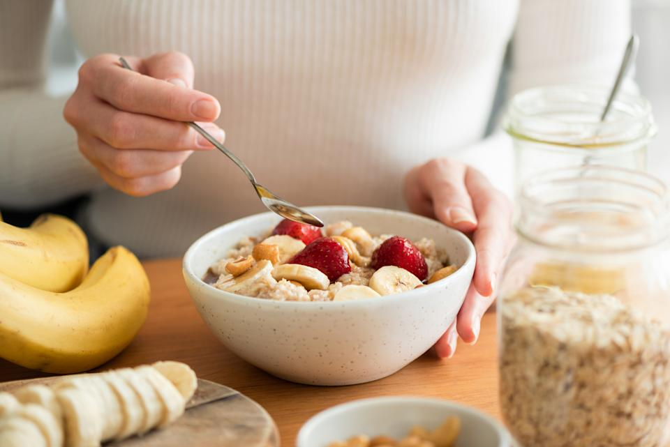Woman eating oatmeal porridge with banana, strawberries and nuts. Healthy breakfast at the sunny morning kitchen table